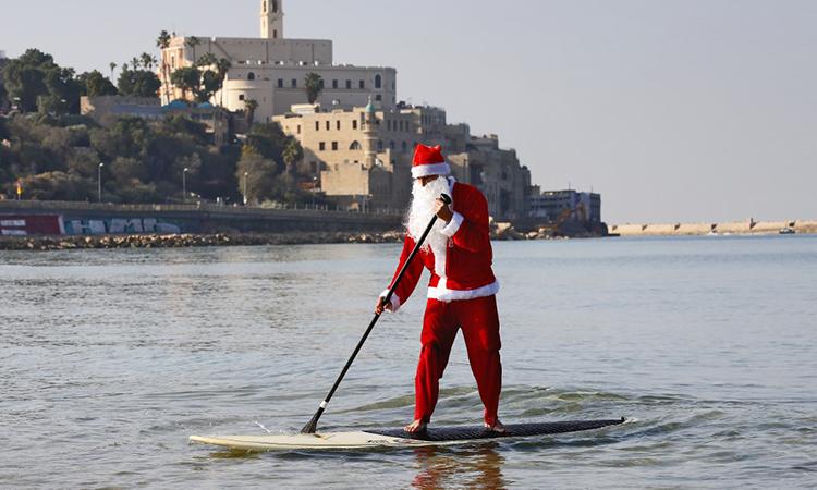 'Ông già Noel' cưỡi ván lướt sóng đi phát quà