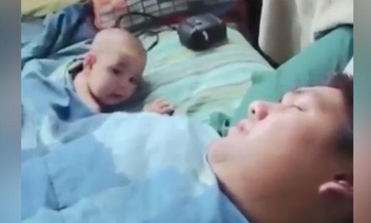 Bé trai giật mình khi ngủ cùng bố