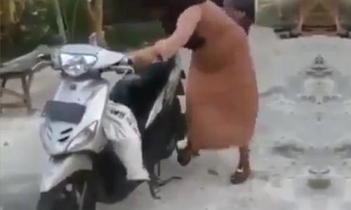 Người phụ nữ cố đạp khởi động xe tay ga khi chống chân