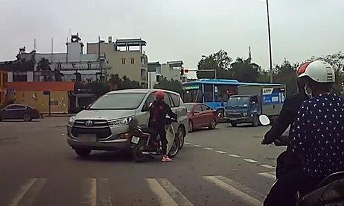 Cô gái đi xe máy dừng đèn đỏ không quan sát