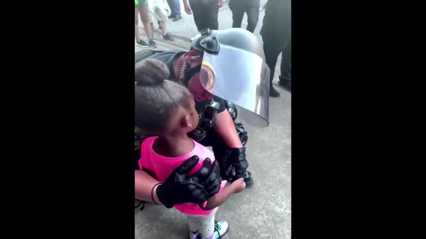 Cảnh sát ôm bé gái da màu