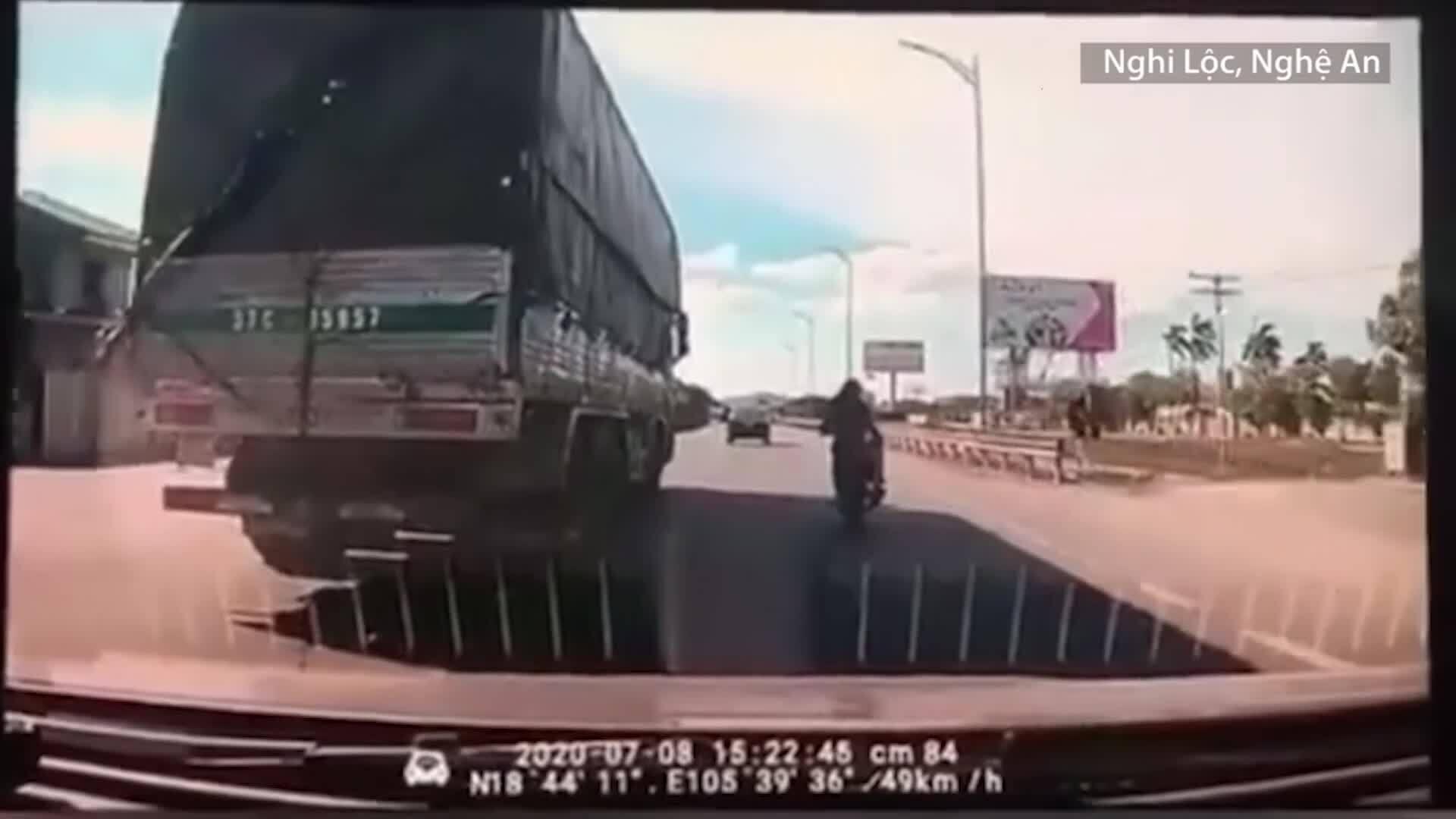 Xe máy đi sát xe tải để tránh nắng