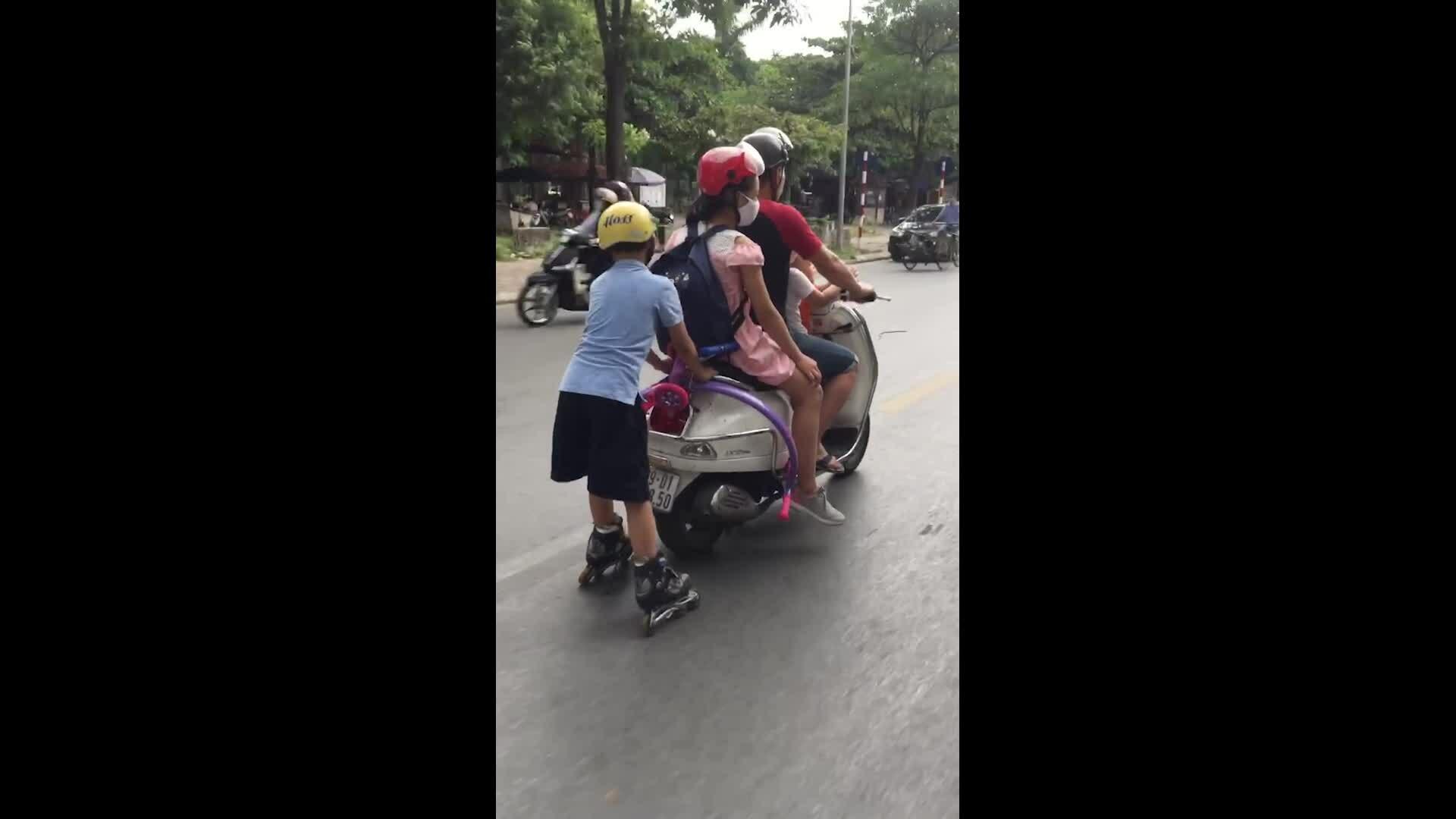 Xe máy chở ba kéo theo một đứa trẻ