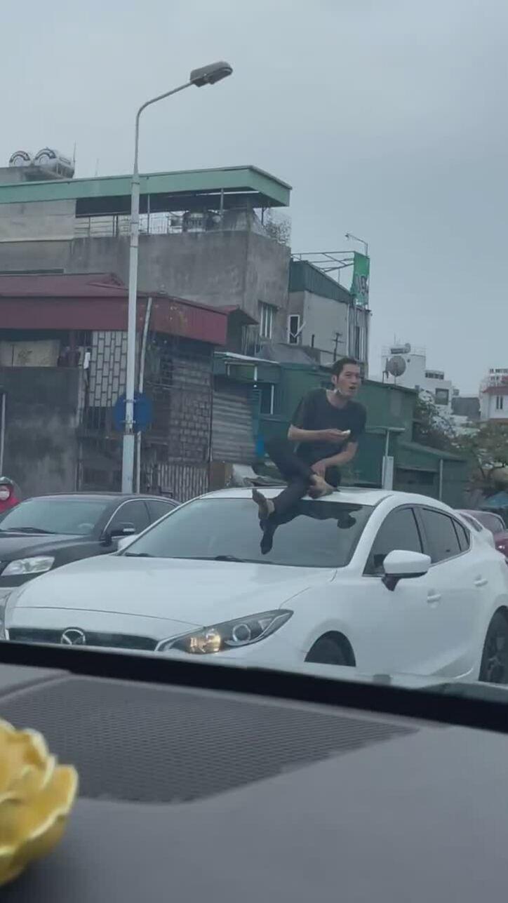 Nam thanh niên leo lên nóc ôtô ngồi