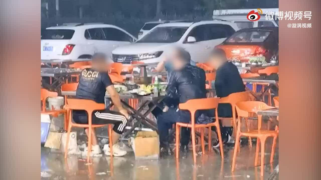 Bốn thanh niên ngồi ăn lẩu dưới mưa