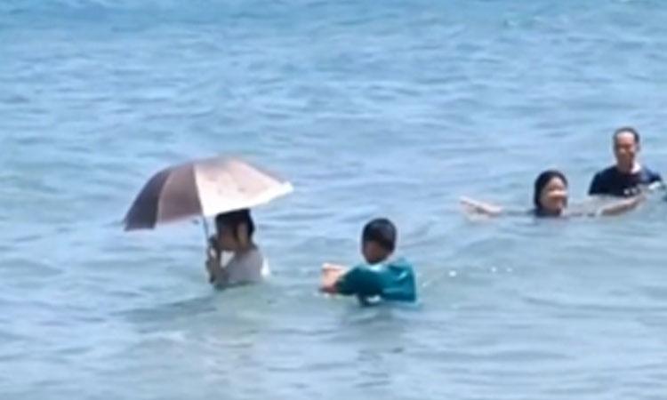 Cô gái mang ô khi tắm biển