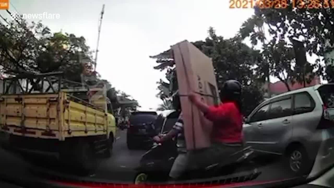 Người đi xe máy làm rơi tivi vì luồn lách