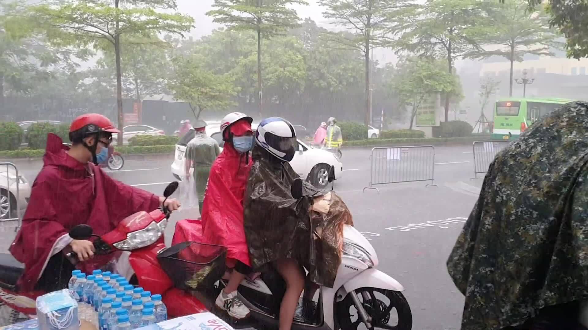 Phụ huynh đưa con đến điểm thi trong mưa lớn