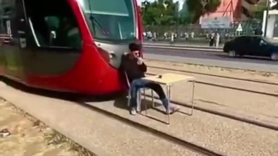 Thanh niên ngồi uống cà phê chặn đầu tàu điện