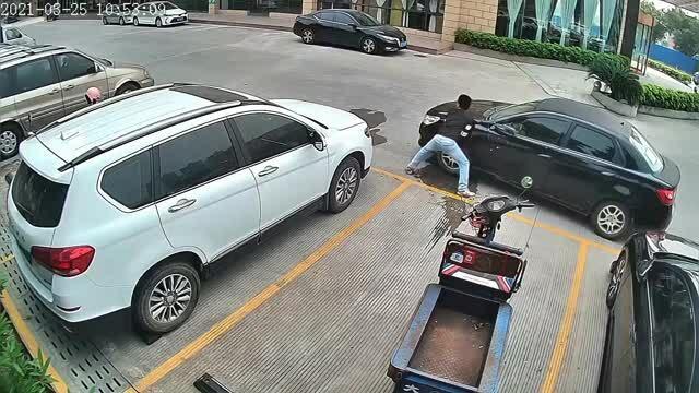 Người đàn ông dùng tay đẩy ôtô đỗ chắn đường