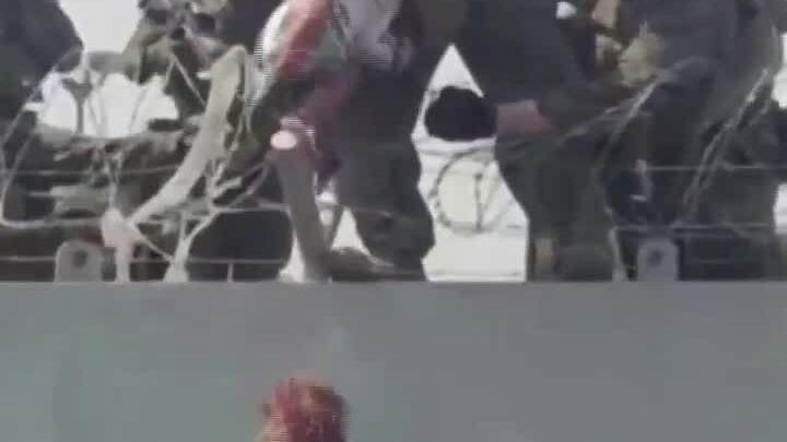 Lính Mỹ nâng em bé Afghanistan qua hàng rào dây thép gai