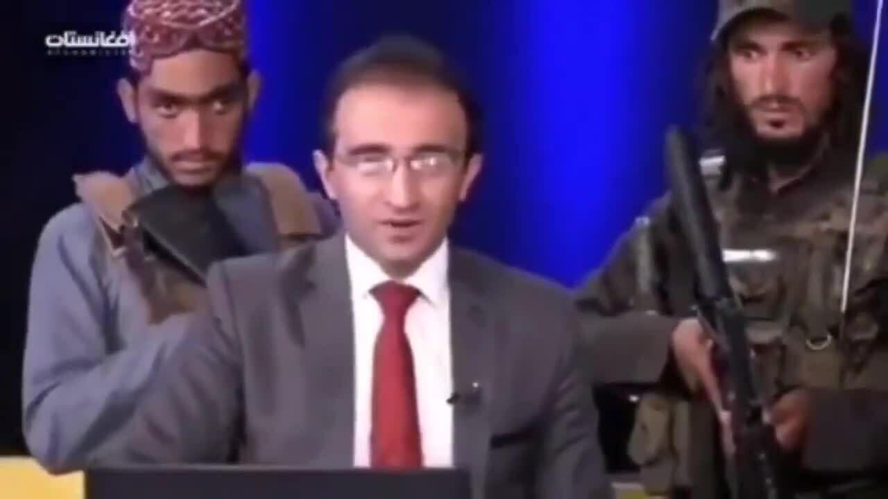 Thành viên Taliban ôm súng vây quanh người dẫn chương trình